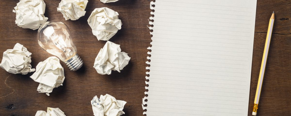 Paper and pencil with glowing light bulb among the crumpled rubbish for writing concept