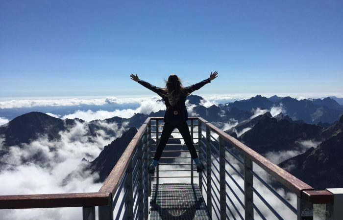 person standing over mountain stairs with hands raised