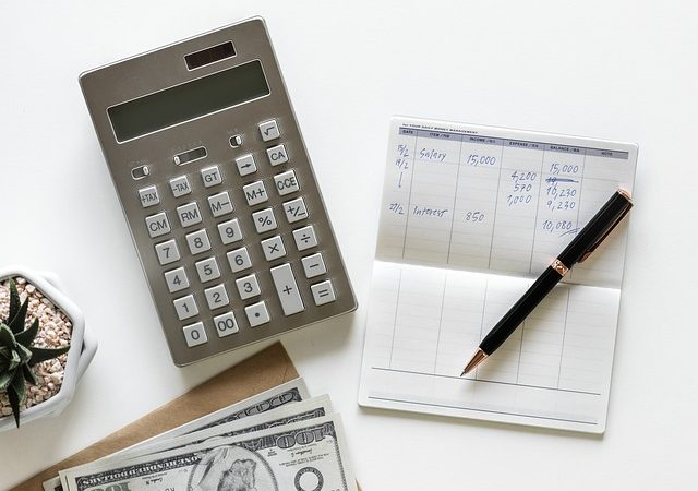 calculator surrounded by money and check book