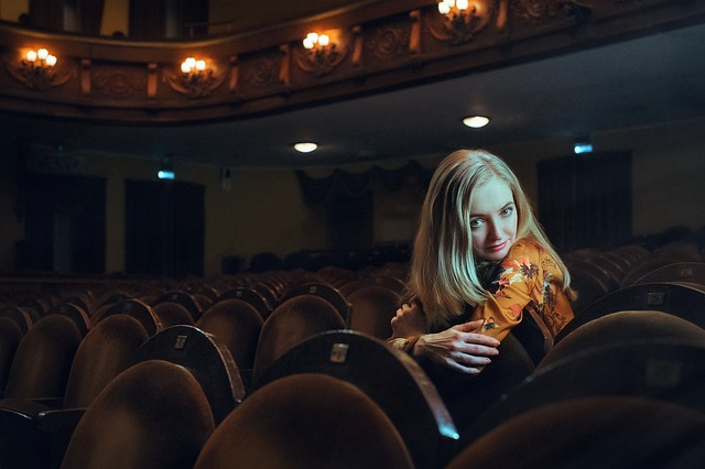 girl sitting on a seat in a theater