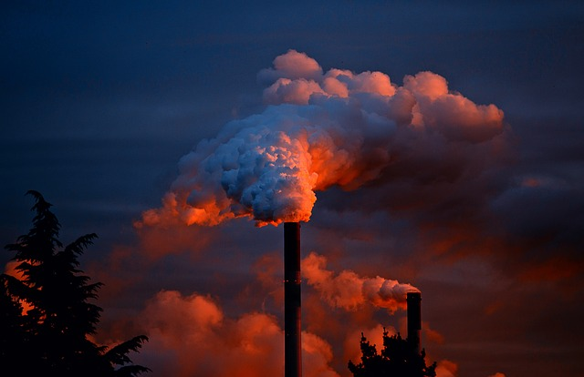 factory with smoke at sunset