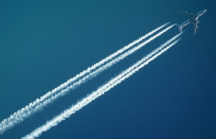 an airplane flying in the sky with a trail