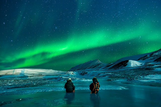 two people looking at an aurora in the sky