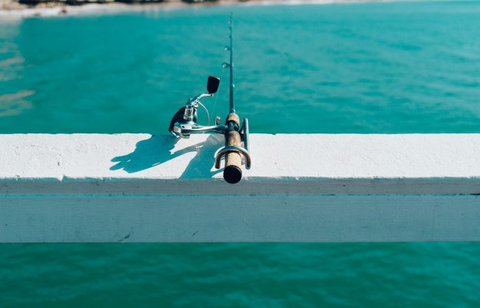a fishing pole on a ledge over water