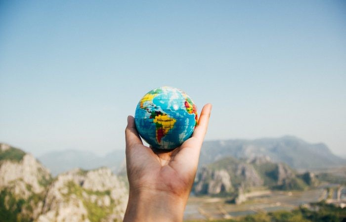 hand holding globe before a landscape background