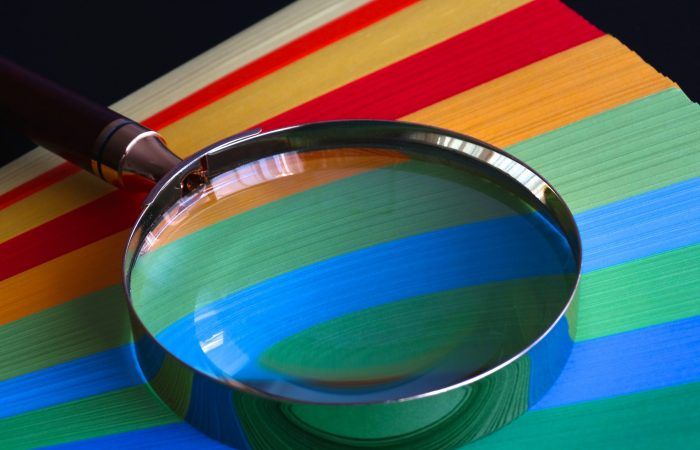 a magnifying glass on top of colored paper