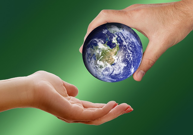 someone handing a small globe to another person