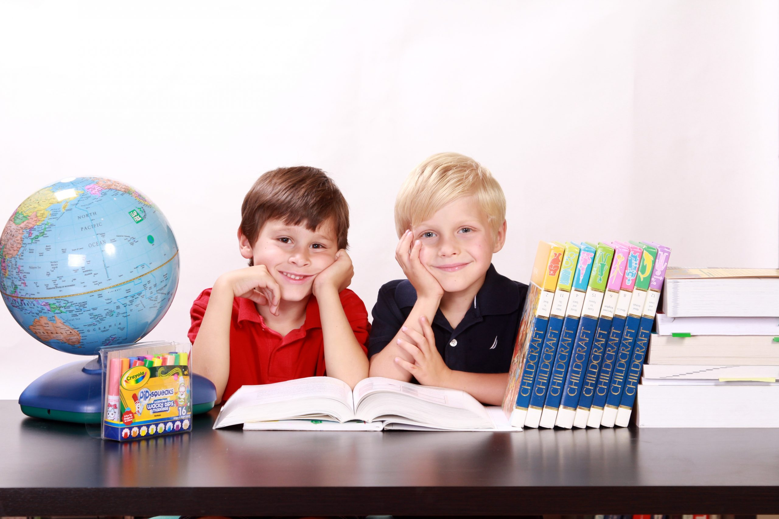 two kids with globe and school supplies