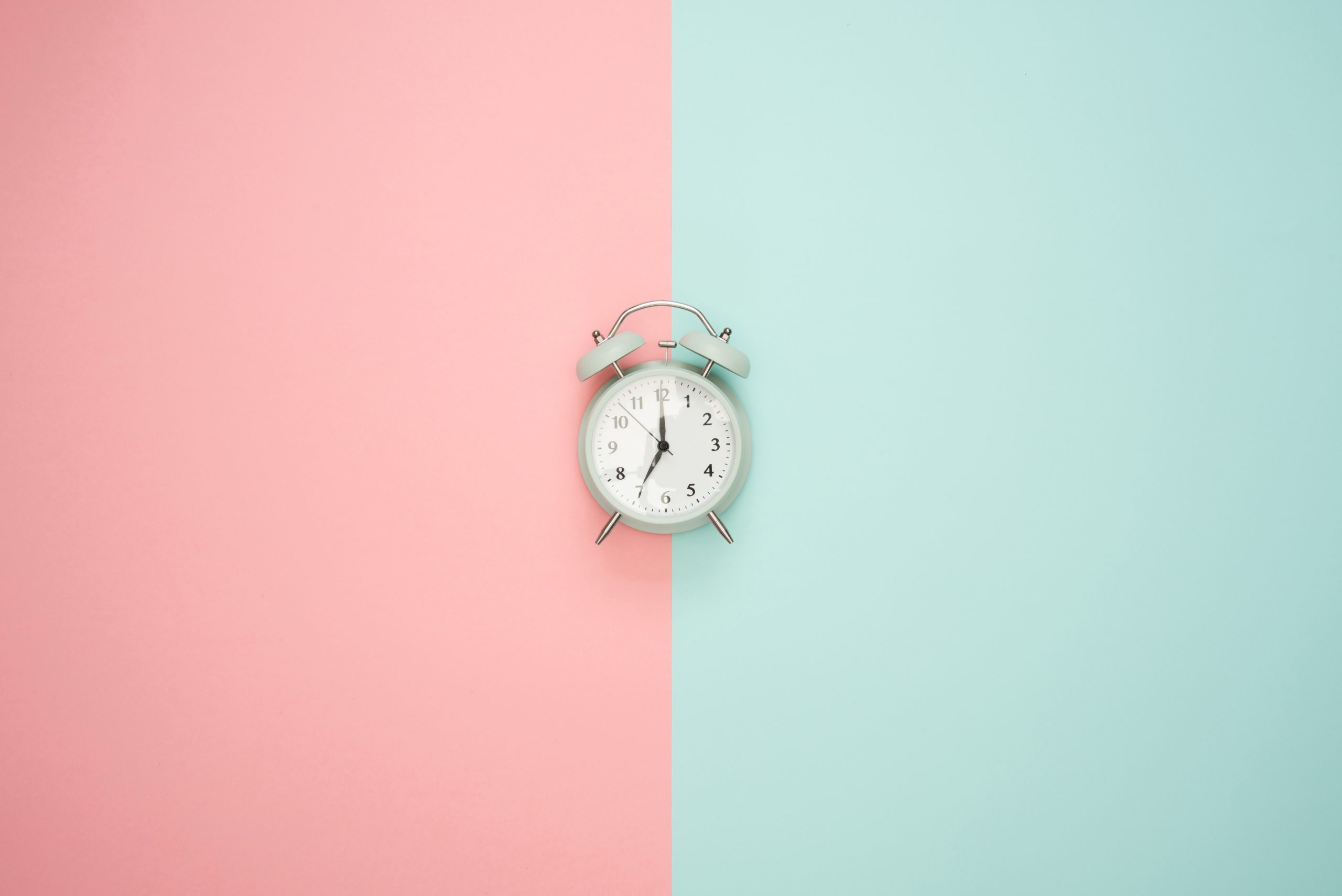 Alarm clock with pink and blue background.