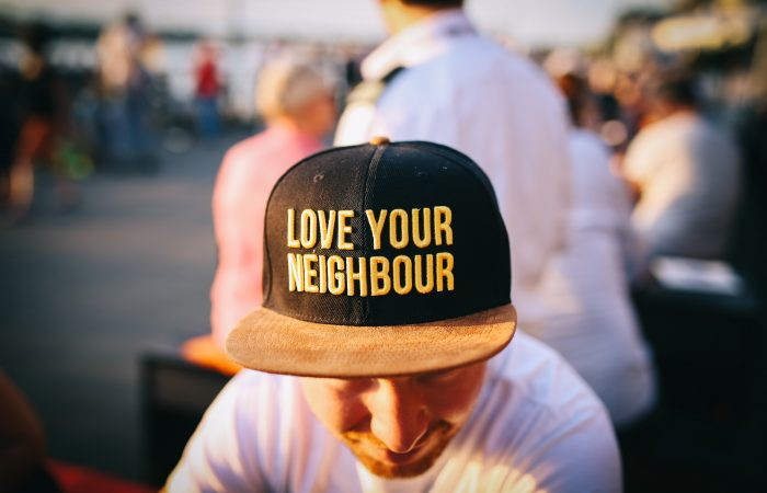 Person with a hat with the words 'Love your neighbour.'