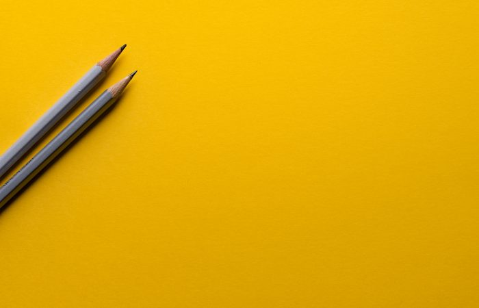 Two pencils with yellow background.