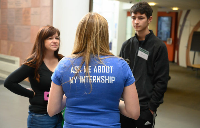 Student doing internship talking to two students