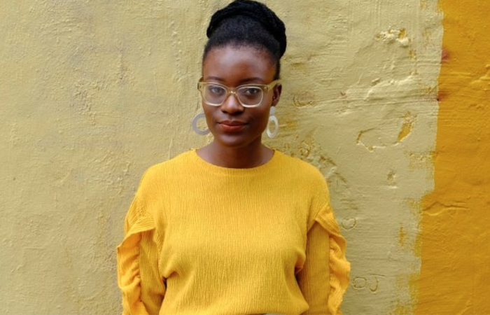 Black woman with glasses standing in front of yellow mural