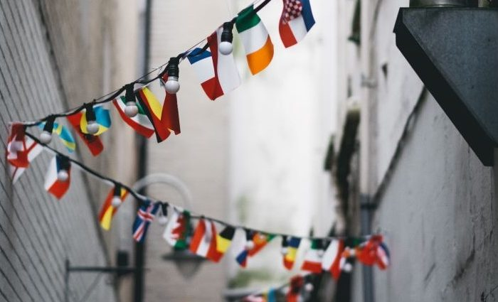 flags of different nations hanging in an alleyway