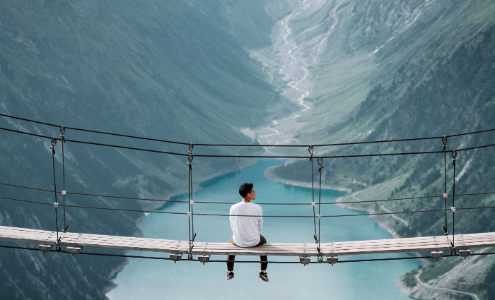 person sitting on bridge over water