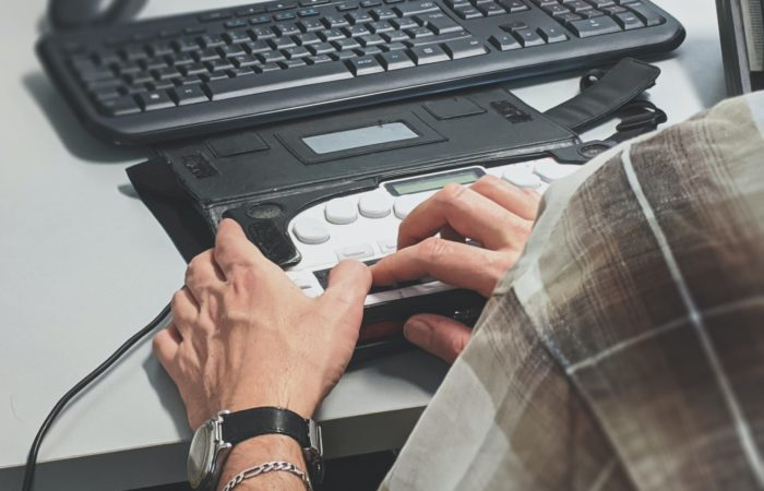 person using assistive technology - hands on a computer keyboard